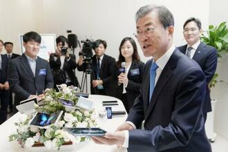 10日、サムスングループのディスプレー工場を訪問し、次世代ディスプレー製品を体験する韓国の文在寅大統領(手前)=韓国・牙山(聯合=共同)