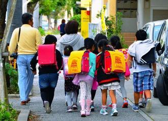 運動場に米軍機の窓が落下した市立普天間第二小学校から下校する児童ら=13日午後、沖縄県宜野湾市