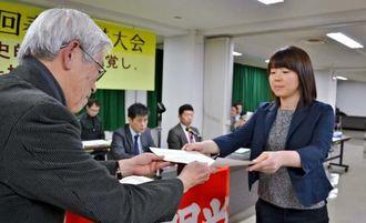 「新聞労連ジャーナリズム大賞」優秀賞の賞状を受け取る嘉数よしの記者(右)=東京・文京区民センター