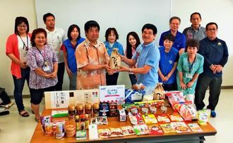 平安座会長(手前右)から宮里課長へ米などが届けられた=5日、沖縄市社会福祉協議会