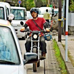オートバイで被災現場を調査して回る前原土武さん=16日午前11時20分ごろ、熊本県益城町内