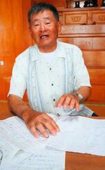 自身の戦争体験や、空襲で燃えた自宅敷地の図説を書いたチラシを見せる新垣誠勇さん。「記憶があるうちに書いておかないとね」=9月30日、南風原町与那覇