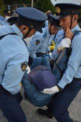 新基地建設に抗議する座り込みの市民を強制排除する機動隊員=27日午前7時、名護市辺野古