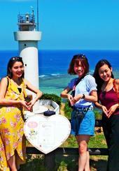 「恋する灯台」と一緒に記念撮影する(左から)又吉夢乃さん、和栗知咲さん、佐藤瞳さん=石垣市平久保・平久保崎灯台