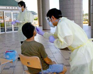PCR検査を受ける男性=12日、北谷町役場玄関前(宮城一彰撮影)