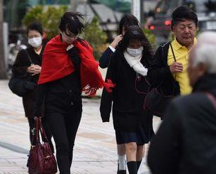 冷たい風の中、足早に横断歩道を渡る人たち=17日午前、那覇市久茂地