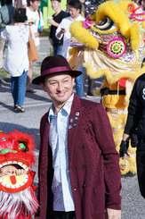 パレードに参加し、笑顔で記念撮影に応じるちゃんぶる~沖縄市大使のISSAさん=24日午後、沖縄市・コザゲート通り(下地広也撮影)