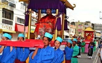 国王を中心とした普天満御参詣の一行が宜野湾市普天間の中心地を練り歩いた(屋良朝輝撮影)