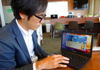 パソコン画面に表示したRPG「SPARX」を説明する徳里政亮さん=浦添市・BowL