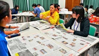気になる記事を互いに紹介する参加者=20日、本部町の沖縄美ら島財団