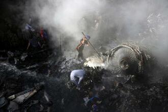 パキスタン航空(PIA)の旅客機が墜落した現場で生存者を捜すボランティアたち=22日、パキスタン・カラチ(AP=共同)