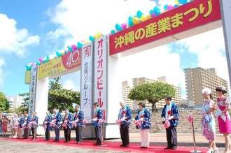 第40回沖縄の産業まつりの開会式でテープカットする主催者ら=21日午前10時半、那覇市・奥武山公園