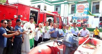 国際協力で、フィリピン・ビクトリアス市へ消防車や救助艇を寄贈する島尻消防管理者の古謝景春南城市長(前列左から6人目)ら=2月15日、ビクトリアス市役所前広場(提供)