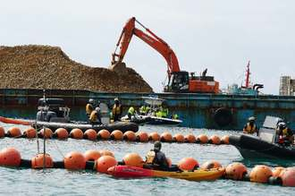 「K9」護岸に接岸した台船から土砂を陸揚げするショベルカーと海上で抗議するカヌー(手前)=7日、名護市辺野古沖