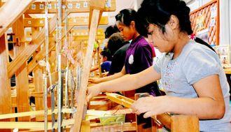 お父さんに感謝の気持ちを込めて久米島紬コースターを織る町内の子どもたち=久米島紬の里ユイマール館