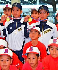 チームメイトに囲まれ優勝メダルを掲げる宇地原丈智(左)と福原聖矢=15日、那覇空港