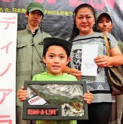 「ディノアライブ」展の1万人目の来場者レモラ・サージョン君と母親の美津枝さんら=3日、豊見城市のとみとん