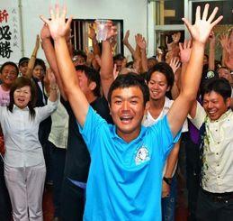 20代の若者らとバンザイで当選を喜ぶ長山家康さん(中央)=7日午後11時46分、石垣市登野城