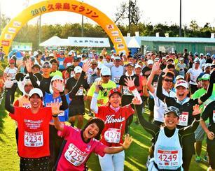 朝日を浴びながら一斉にスタートするフルマラソンの参加者=23日午前7時半、久米島町営仲里野球場(金城健太撮影)