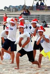 照りつける日差しの下、サンタの帽子をかぶりトレーニングをする宜野湾高校野球部の選手たち=24日午後、北谷町・サンセットビーチ(喜屋武綾菜撮影)