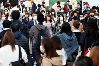 東京・渋谷のスクランブル交差点をマスク姿で行き交う人たち=20日午後