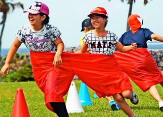 デカパン競争で笑顔で走る児童たち=4月28日、本部町・海洋博公園