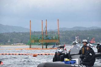 掘削棒が海に下りた状態のスパット台船(奥)。台船上に作業員の姿は見られない=28日午前、名護市辺野古沖の長島付近