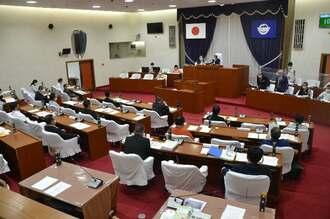条例の可決を受けて頭を下げる市幹部ら(右奥)=26日、宜野湾市議会