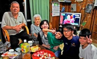 糸数陽一さんのリオ五輪出場を祝い、手製のすしを食べて喜ぶ母親幸子さん(右から4人目)と祖父母、きょうだい=28日、南城市知念知念