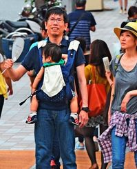 蒸し暑さをうちわでしのぐ歩行者=17日午後5時ごろ、那覇市・むつみ橋交差点(国吉聡志撮影)