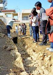 石積みで造られた排水溝の遺構を前に、調査員から説明を受ける参加者=那覇市首里・城西小学校