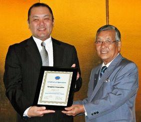 米国日系レストラン協会の波多野勳会長(右)から感謝状を受けた砂川社長=ロサンゼルス市、ダブルツリーホテル