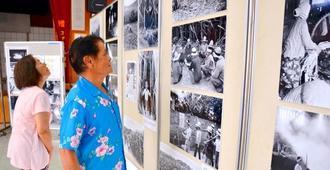 82年前に撮られた写真に見入る地元の人たち=14日、沖縄市・古謝公民館