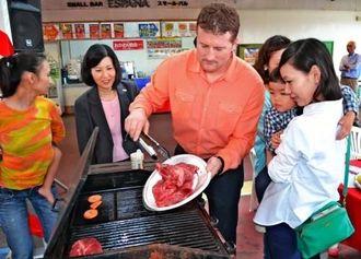 参加者と一緒にカナダビーフを調理するロブ・メイヤー会長(中央)=21日、那覇市・エスパーナ