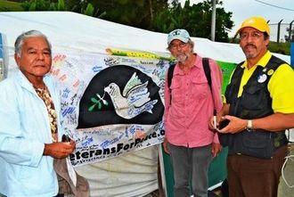 米軍の退役軍人らでつくる「ベテランズ・フォー・ピース」のエドワルド・ハインリック・サンチェスさん(右)とダグラス・ラミスさん(中央)。寄せ書きを贈られた中村司さん=21日、名護市辺野古・キャンプシュワブゲート前