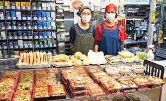 一丁目ストアーで深夜に働く従業員ら。深夜帯でも多くの弁当やサンドイッチなどが並ぶ=10日、沖縄市上地