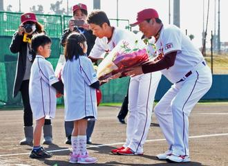 歓迎の花束を(右から)梨田監督と岡島選手会長に渡す金城ちゃん、松堂君=金武町ベースボールスタジアム