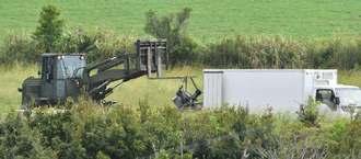 解体したヘリ残骸をフォークリフトでつり上げ、トラックに載せる米軍関係者=19日午後1時11分、東村高江(渡辺奈々撮影)