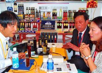 棚を使って商品をきれいに並べ、PRする二反田醤油店蔵の担当者(左)=27日、宜野湾市・沖縄コンベンションセンター