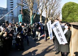 「不当判決」と書かれた垂れ幕を掲げる住民側の弁護士=21日午後、東京高裁前