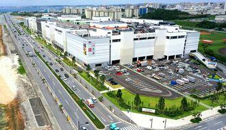 27日に開業するパルコシティ(右)。手前から奥に延びるのは西海岸道路=21日、浦添市西洲(小型無人機で撮影)