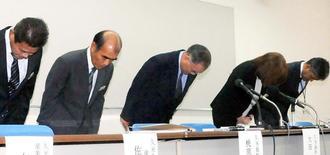 久米島町職員による公金横領疑い事件について、会見で謝罪する大田治雄町長(中央)ら=18日、同町役場