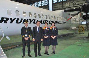 那覇空港に到着した新機材「Q400CC」を紹介する伊礼恭社長(左から2人目)=19日、那覇空港