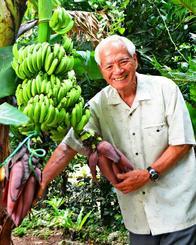 一つの茎に二つの花を付けた「双子バナナ」を育てた前田士門さん=本部町新里