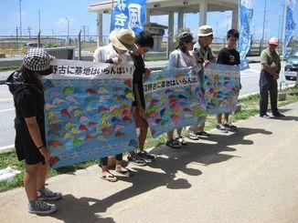ジュゴンの折り紙に書いた多数の応援メッセージを披露する長崎県からの参加者たち=19日午前11時27分、名護市辺野古の米軍キャンプ・シュワブゲート前