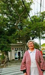 ガジュマルに覆われた照喜名商店と店主の照喜名ヨシ子さん。首里と与那原を結ぶ道路に面し、木陰で人々が休んだという=5日、南風原町大名