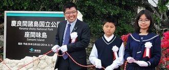 国立公園指定を記した記念碑を除幕した宮里哲村長(左)ら関係者=9日、座間味村