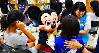 子どもたちにハグをするミッキーマウス(中央)と、アンバサダーの福本望さん(右端)=8日、市知花の「美さと児童園」