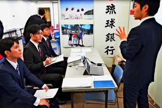 企業担当者の説明に耳を傾ける大学生ら=日、東京・西新宿の新宿住友ビル