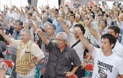 日米地位協定の抜本的な改正を求め、気勢を上げる抗議集会の参加者=6月25日午後、北中城村立中央公民館